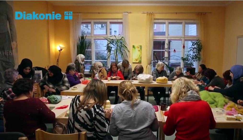 Frauengruppe sitzt an Tischen bei Kreativ-Café